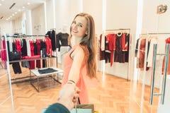 Женщина волоча ее человека для того чтобы фасонировать покупки в бутике или магазине Стоковые Изображения