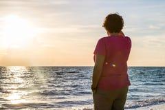 Женщина восхищая заход солнца Стоковые Изображения RF