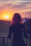 Женщина восхищая заход солнца от ее балкона Стоковая Фотография RF