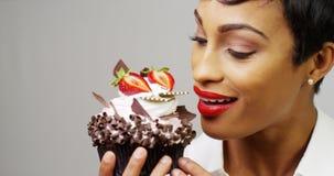 Женщина восхищая причудливое пирожное десерта с шоколадом и клубниками Стоковые Изображения