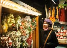 Женщина восхищая самый лучший венок рождественской ярмарки Стоковая Фотография