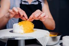 Женщина во время делать украшая торт стоковые фотографии rf