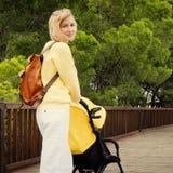 Женщина волос Blong идя в парк с прогулочной коляской Стоковая Фотография RF