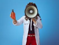 Женщина врача со сливк солнца показа мегафона на сини стоковые фото