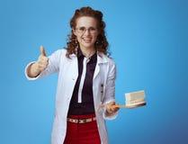 Женщина врача с баром мыла и щетка ванны показывая большие пальцы руки вверх стоковая фотография rf