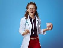 Женщина врача с ликованием копилки на сини стоковое фото