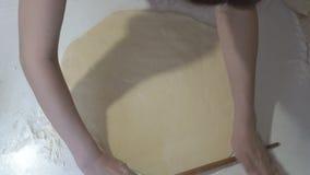 Женщина вращающей оси дома деревянной свертывает тесто в форму круга на белой таблице акции видеоматериалы