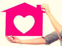 Женщина вручает владениям красный бумажный дом с формой сердца стоковое изображение