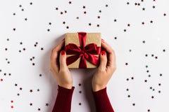 Женщина вручает держать коробку праздничного подарка рождества на украшенной праздничной таблице Стоковые Фото