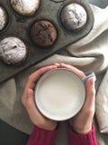 Женщина вручает держать чашку молока около стола с булочками Стоковое Изображение