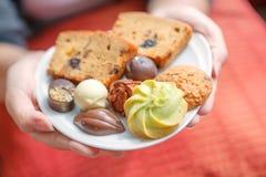 Женщина вручает держать белую плиту печений, шоколада и хлеба Стоковые Изображения