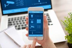 Женщина вручает держать телефон и тетрадь с домом app умным Стоковая Фотография RF