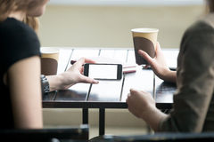 Женщина вручает держать телефон с белым пустым экраном в кафе C Стоковое Изображение