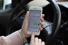 Женщина вручает держать iPhone 6S с такси Uber применения Стоковое фото RF