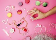 Женщина вручает держать macaroons с серией вещества девушки на розовой предпосылке, концепции аксессуаров девушек Стоковое Фото