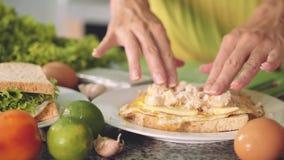 Женщина вручает делать сандвич с яичком, сыром, цыпленком и зеленым салатом сток-видео