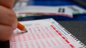 Женщина вручает заполняя удачливый номер на билете лотереи 649