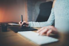 женщина вручает печатать на машинке клавиатуры Молодая женщина используя цифровые графическую таблетку и ручку чертежа для нового Стоковая Фотография