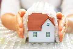 Женщина вручает покрывать модельный дом с предохранением от дома wrap- пузыря или концепцией страхования стоковые фотографии rf