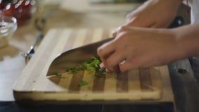 Женщина вручает прерывать зеленый vegetable салат на разделочной доске, вегетарианской еде акции видеоматериалы