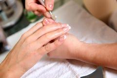 женщина вручает процесс manicure Стоковое Фото