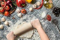 Женщина вручает разворачивание тесто на предпосылке металла, конце вверх Шеф-повар делает тесто Таблица с овощами и kitchenware Стоковое Фото