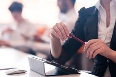 Женщина вручает ручку удерживания на деловой встрече Стоковая Фотография