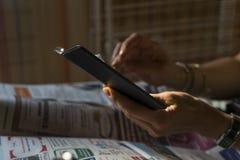 Женщина вручает удержание мобильного смартфона и выстукивает на ей Конец черного телефона острый вверх с запачканной предпосылкой стоковые изображения