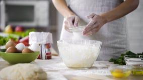 Женщина вручает фильтровать муку над стеклянным шаром при тесто, добавляя ингридиенты выпечки стоковая фотография rf
