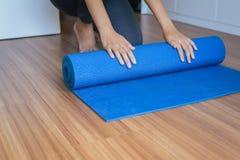 Женщина вручает циновку после разминки, оборудование йоги завальцовки или складчатости тренировки стоковые фото