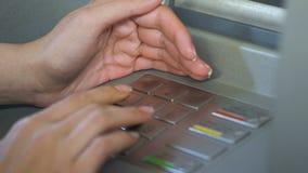 Женщина входя в ее код штыря и пряча клавиатуру банкомата сток-видео