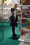Женщина выбирает выставку ботинок ботинок модным специализированную International для обуви, сумок и ботинок Москвы Mos аксессуар Стоковые Фотографии RF