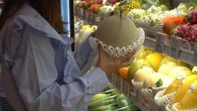 Женщина выбирает дыню, которая помещена на полке видеоматериал
