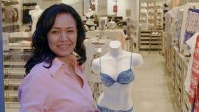 Женщина выбирает нижнее белье на бутике стоковая фотография