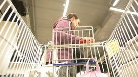 Женщина выбирает плодоовощи Абстрактное неясное изображение торгового центра и людей Предпосылка взгляда магазинной тележкаи defo сток-видео