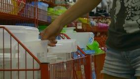 Женщина выбирает утварь кухни видеоматериал