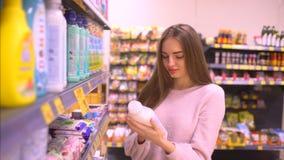 Женщина выбирает химикаты домочадца в магазине женщина выбирает умягчитель на супермаркете сток-видео