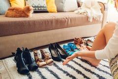 Женщина выбирая ботинки дома Трудный выбор, который нужно сделать из сандалий, пяток и квартир стоковые изображения