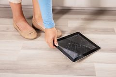 Женщина выбирая вверх сломленную таблетку цифров стоковые фотографии rf