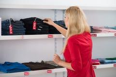 Женщина выбирая джинсы в магазине Стоковое фото RF