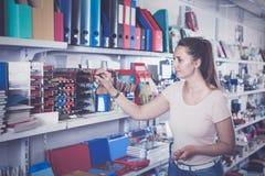 Женщина выбирая карандаш цвета, тетрадь с прописями другого цвета в станции Стоковые Фотографии RF