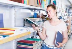 Женщина выбирая карандаш цвета, тетрадь с прописями другого цвета в станции Стоковые Изображения