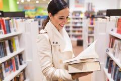 Женщина выбирая книгу в Bookstore Стоковые Изображения RF
