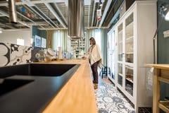 Женщина выбирая мебель кухни Стоковое Фото