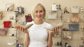 Женщина выбирая между подобными ботинками стоковые фото
