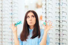 Женщина выбирая между стеклами и контактными линзами в магазине оптики стоковые фото