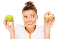 Женщина выбирая между яблоком и донутом Стоковое Изображение