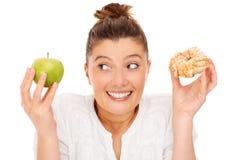 Женщина выбирая между яблоком и донутом Стоковое Изображение RF