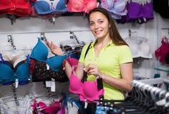 Женщина выбирая нижнее белье в магазине Стоковое Фото