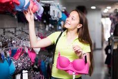 Женщина выбирая нижнее белье в магазине Стоковые Фото